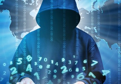 Cybercrime Stock Photo showing a Blue Hooded Hacker at a Keyboard