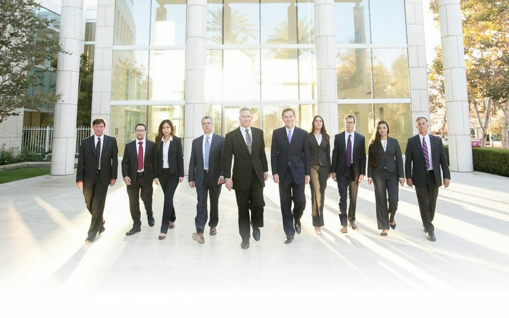 injury attorneys anaheim ca group photo 10 people in black suits yellow