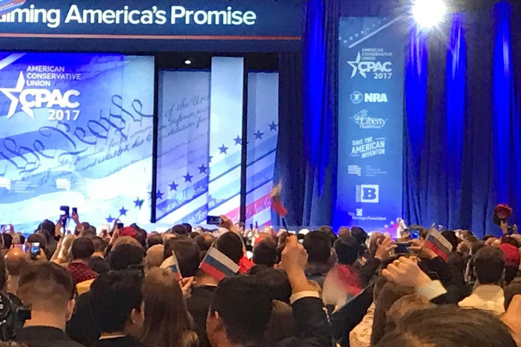 CPAC attendees waives Russian flags as part of a hoax.  Image Source: people.com