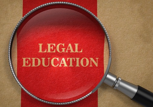 Picture of a Magnifying Glass over the Phrase Legal Education on a Red Background