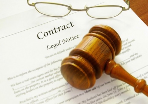 Picture of a Wooden Gavel and a Pair of Glasses Lying on a Legal Contract