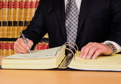 Stock Image of an Attorney in a Law Library Writing in a Large Legal Binder at a Table